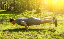 Young athletic man balancing while doing two hand push up and holding body in air. Caucasian sportsman competing on green field in forest. Outdoors warm up royalty free stock photography