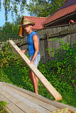 Young athletic man in balomenou hat puts a pine Board on the sta Royalty Free Stock Photography