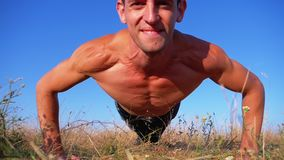 Young athletic man with a bare torso performs push-ups with claps on nature. Slow motion. In 180 fps. man doing calisthenics workout on the meadow. Outdoors stock video footage