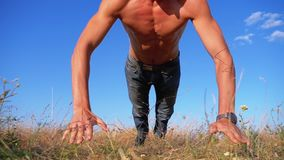 Young Athletic Man with a Bare Torso Performs Push-ups with Claps on Nature. Slow Motion. In 180 fps. Man doing calisthenics workout on the meadow. Outdoors stock footage