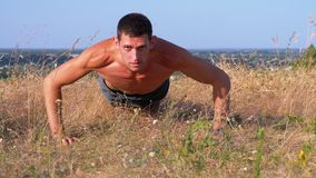 Young Athletic Man with a Bare Torso Performs Pushups on the Nature. Young Athletic Man with a Bare Torso Performs Pushups on Nature. Man doing calisthenics stock video