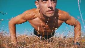 Young athletic man with a bare torso performs pushups on the nature. Slow motion. Young athletic man with a bare torso performs pushups on nature. Slow motion in stock footage