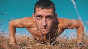 Young athletic man with a bare torso performs pushups on the nature. Slow motion. Young athletic man with a bare torso performs pushups on nature. Slow motion in stock video