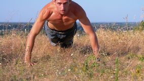 Young athletic man with a bare torso performs pushups on the nature. Young athletic man with a bare torso performs pushups on nature. Man doing calisthenics stock footage