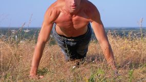 Young Athletic Man with a Bare Torso Performs Pushups on the Nature. Young Athletic Man with a Bare Torso Performs Pushups on Nature. Man doing calisthenics stock video footage
