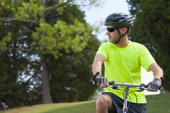 Young athletic man on bicycle. A young man rides a bicycle outside on a hot summer day royalty free stock image