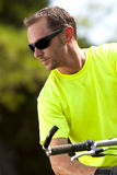 Young athletic man on bicycle. A young man rides a bicycle outside on a hot summer day stock image