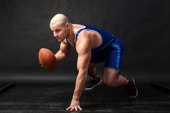 A young athletic man holds a brown rugby ball. A young athletic man in blue wrestling tights and blue shorts stands in a low position and holds a brown rugby royalty free stock photos