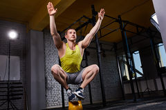Young athletic man doing exercises in cross fit gym while crouching on two legs on the kettlebell. Sportsman in the sportwear, yellow t-shirt, shorts and Stock Photo