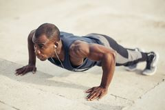 Portrait of a young black man doing push ups at the beach Royalty Free Stock Image