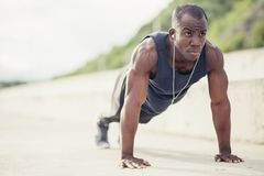 Portrait of a young black man doing push ups at the beach stock photos