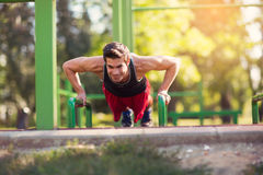 Young athletic man doing push ups outdoors. Stock Images