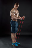Young athletic man exercising. And doing fitness with a chest expander, resistance band, on dark background Stock Photo