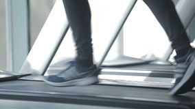 Dnipro March 2017. Young athletic man running on treadmill in sport gym. Young athletic man exercising and running on treadmill in sport gym. Cardio workout stock video