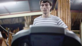 Young athletic handsome man exercising and running on treadmill in sport gym. 1920x1080, hd. Young athletic man exercising and running on treadmill in sport gym stock footage