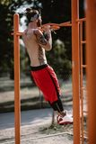 Young athletic man in headband with naked torso dressed in black leggings and red shorts pulls up on the horizontal bar stock image