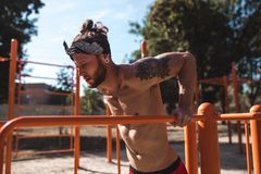 Young athletic man in headband with a naked torso with tattoos doing push-ups on the uneven bars outside on a sunny day stock image