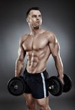 Young athletic man holding two heavy dumbbells Stock Photos