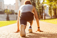 Low start. Young athletic man jogging at morning. Low star. Fitness model in crossfit exercise outdoors. Healthy lifestyle concept Stock Photos