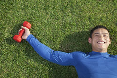 Young Athletic Man Lying Down in Grass with Dumbbells, Directly Above View Royalty Free Stock Image