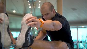 Young athletic man makes stretches exercise in gym stock video footage
