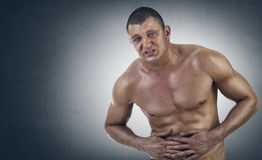 Young Athletic Man in pain. Against a backdrop background Stock Photo