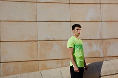 Young athletic man. Portrait of young athletic man standing against brick wall background at sunny day, ready to workout and exercise outdoors royalty free stock photos