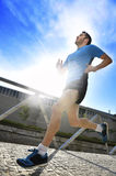 Young athletic man practicing running in urban background backlight in fitness sport training and healthy lifestyle concept. Young athletic man practicing Royalty Free Stock Image