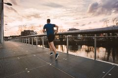 Self overcome conquering obstacles and win. Young athletic man practicing sport outdoors, running fast along bridge over the sunset sky background. Self overcome royalty free stock images