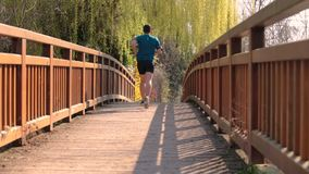 Healthy lifestyle. Young athletic man practicing sport outdoors, running fast along bridge . Self overcome conquering obstacles and win. Healthy lifestyle stock footage