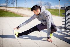 Young athletic man is preparing before running. Royalty Free Stock Photography