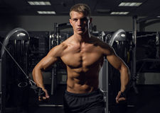 Young athletic man pumping up muscles on crossover Stock Photos