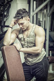 Young athletic man resting on bench in gym Royalty Free Stock Photos