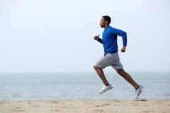 Young athletic man running at the beach Royalty Free Stock Photos