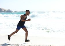 Young athletic man running on the beach Stock Photography