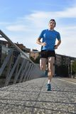 Young athletic man running on blue sky urban city background in sport training Royalty Free Stock Photo