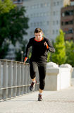 Young athletic man running on urban city park in sport training session Stock Photo