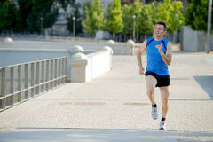 Young athletic man running on urban city park in summer sport training session Royalty Free Stock Photo