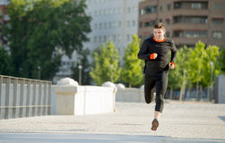 Young athletic man running on urban city park in summer sport training session Stock Photo