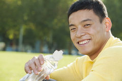Young Athletic Man Sitting on the Grass in a Park, Close Up Stock Image
