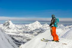Young athletic man skiing on a sunny day with beautiful view of. Athletic man skiing on a sunny day with beautiful view of Matterhorn in the background stock photo