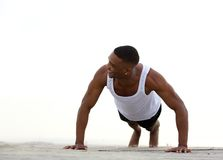 Young athletic man smiling and doing push ups Royalty Free Stock Photo