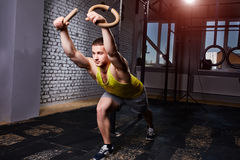 Young athletic man in the sportwear training at the cross fit gym with rings against brick wall. Royalty Free Stock Image