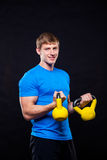 Young athletic man standing with kettlebells on Stock Photo