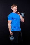 Young athletic man standing with kettlebells on Royalty Free Stock Photo