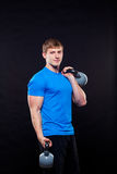 Young athletic man standing with kettlebells on Stock Images