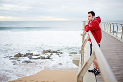Young athletic man standing on the pier rest after. Fitness and healthily lifestyle, sport and healthy concept, jogging and exercise on the beach stock photography