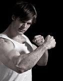 Young Athletic Man with Strong Arms. Portrait of a young strong serious man flexing his muscular arms Royalty Free Stock Photography