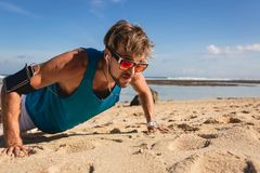 young athletic man in sunglasses doing push ups royalty free stock images
