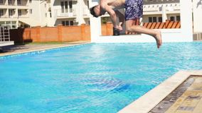 Young athletic man in swim shorts running and jumping spinning to the swimming pool. Slowmotion shot. stock footage